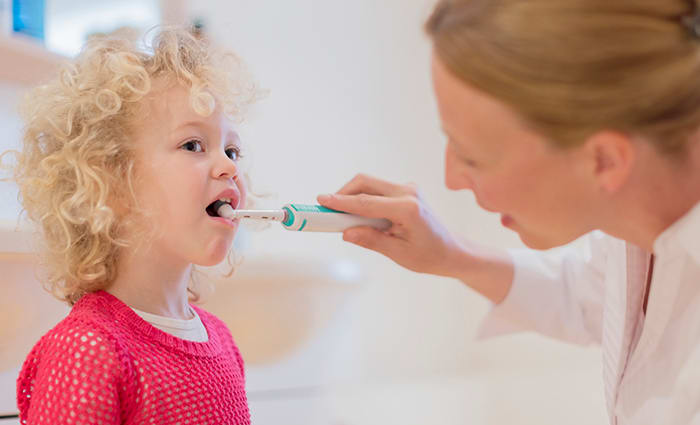 Child Brushing her Teeth with an Electric Toothbrush