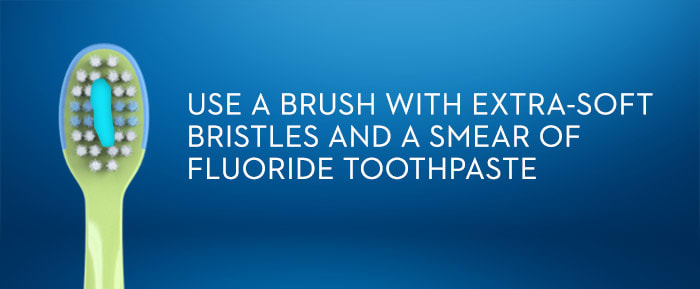 USE A BRUSH WITH EXTRA-SOFT  BRISTLES AND A SMEAR OF FLUORIDE TOOTHPASTE
