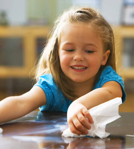 A young girl wipes a brown tabletop using white paper napkins
