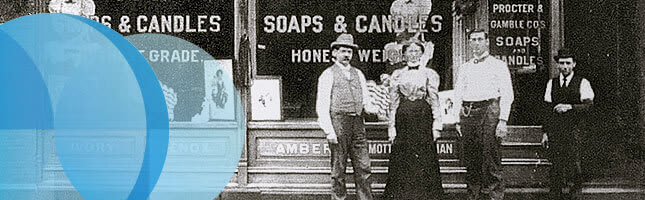 1887 Black and white photograph of men and women in front of a shop