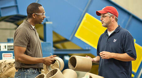 Two men in a factory talk while holding recyclables.
