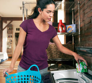 A woman pours Ariel soap into her washing machine as she prepares to do laundry.