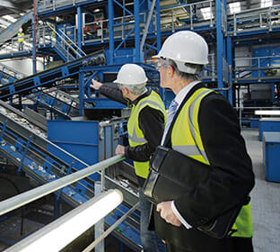 Two men wearing hazard vests and helmets tour a factory.
