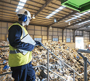 A man wearing a yellow safety helmet and vest holds a clipboard while overseeing a pile of waste.