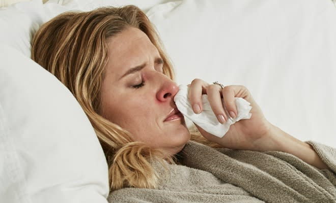 Woman under the weather blowing her nose with Puffs Plus Lotion