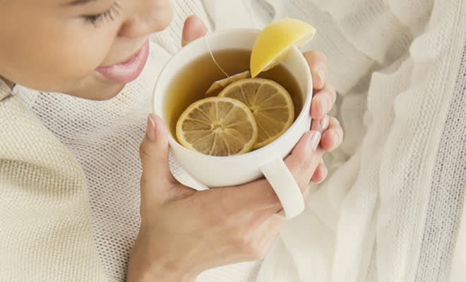 Woman drinking tea with honey and lemon
