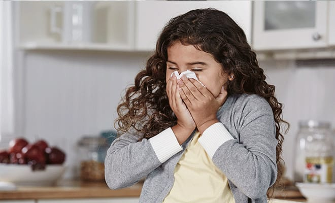 Girl blowing her runny nose in the kitchen with a puffs plus tissue