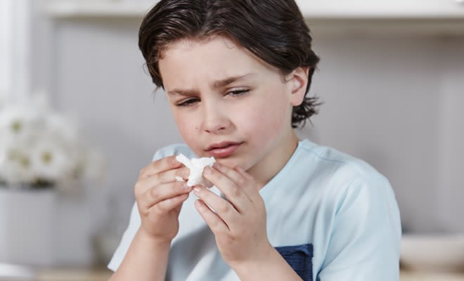 Boy wiping his sore nose with Puffs Plus Lotion