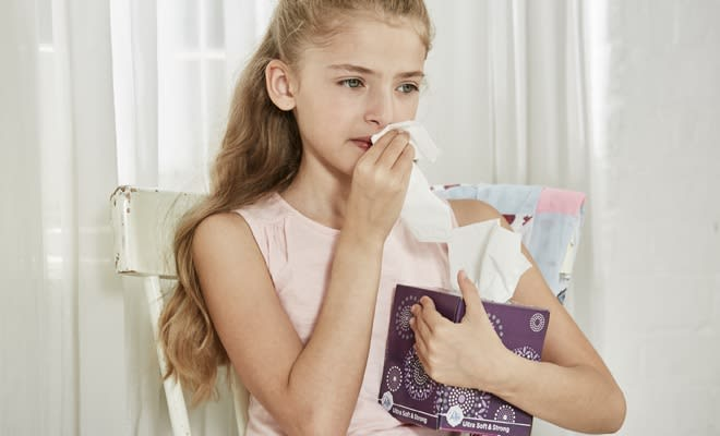 Girl holding a tissue box holder wiping her nose