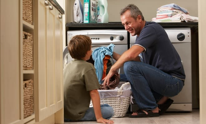 Father showing son how to wash clothes to reduce allergens