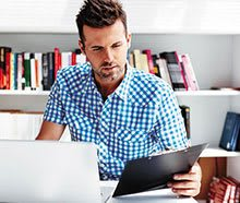 Photo of man looking at paperwork and laptop