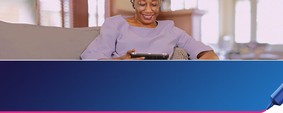 "A woman in her 50s sits on a grey couch reading and iPad and is smiling, The text reads ""Learn more about denture adhesive."""