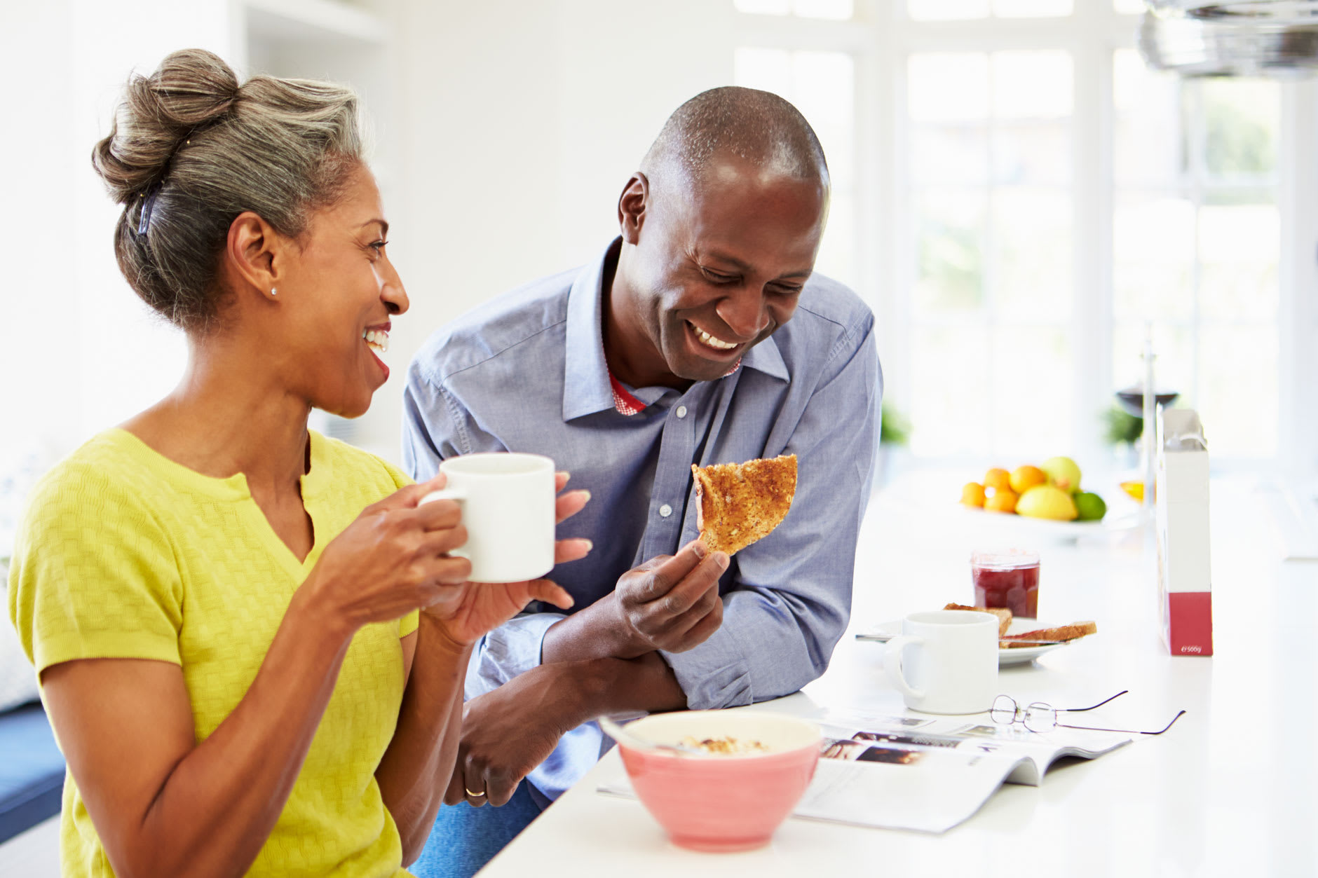 A smiling couple in their 40s are eating pizza and drinking coffee. The man is confident wearing dentures because he has discovered Fixodent's strongest denture adhesive.