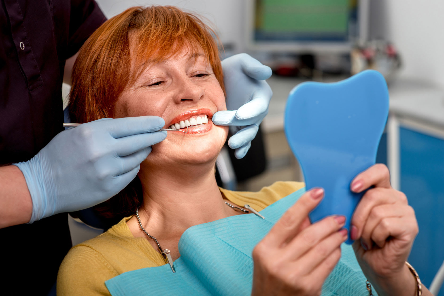 "A woman in her 40s is in the dentist's chair smiling, because she knows the answer to the question ""how long do dentures last"" and ""how to give them a long, happy life"" thanks to Fixodent."
