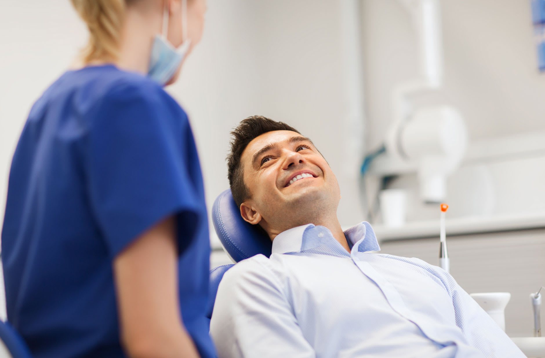 A man in his 30s is smiling in the dentist's chair during a check up as his dentist explains to him that Fixodent denture adhesive can help with how to get rid of denture sores.