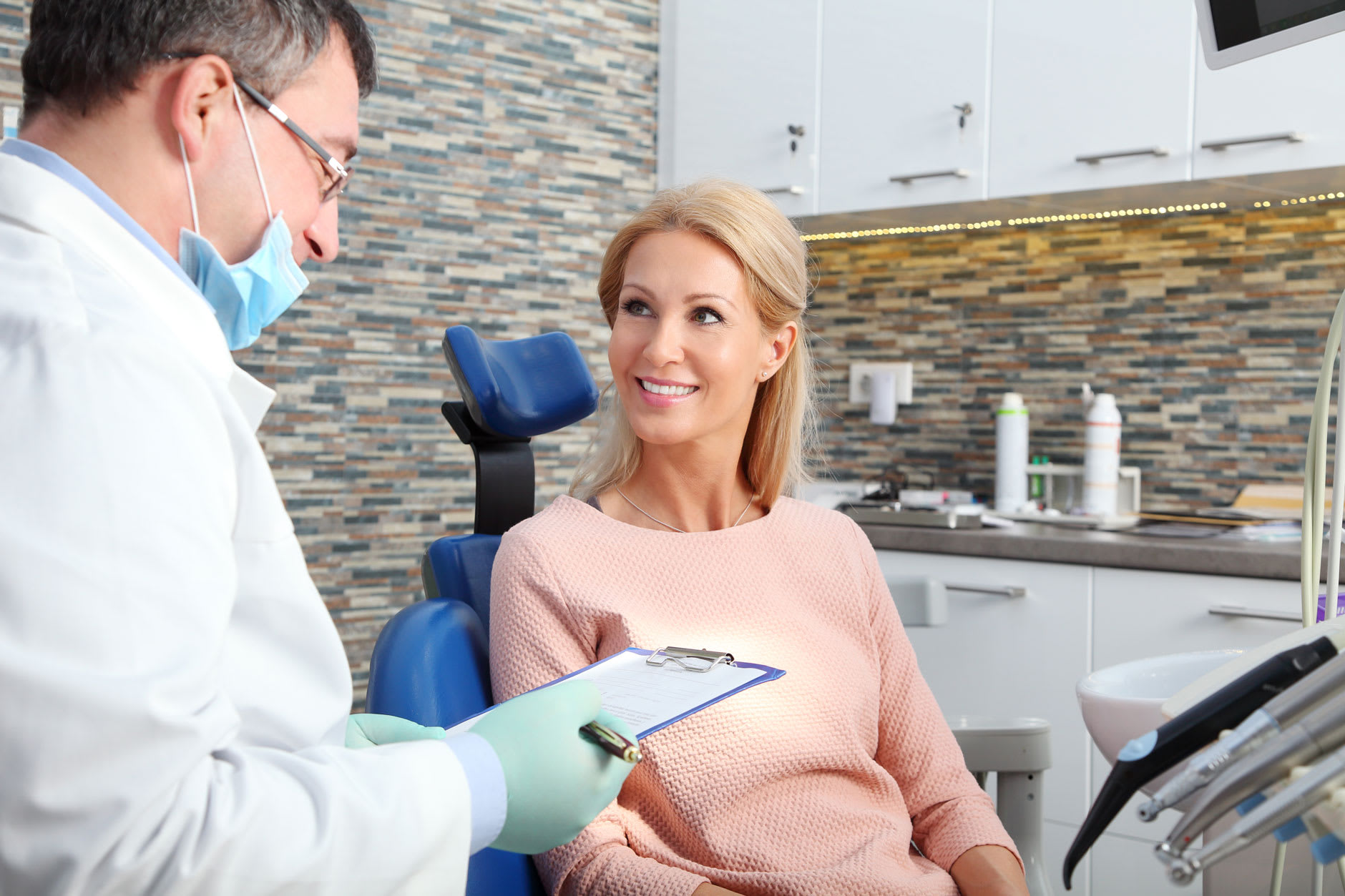 A male dentist explains what is going to happen in the tooth extraction process to a female patient.