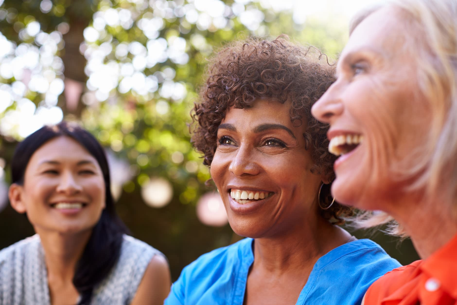 Three women in their 40s and 50s are sitting in a garden smiling and chatting about how much do dental implants cost.