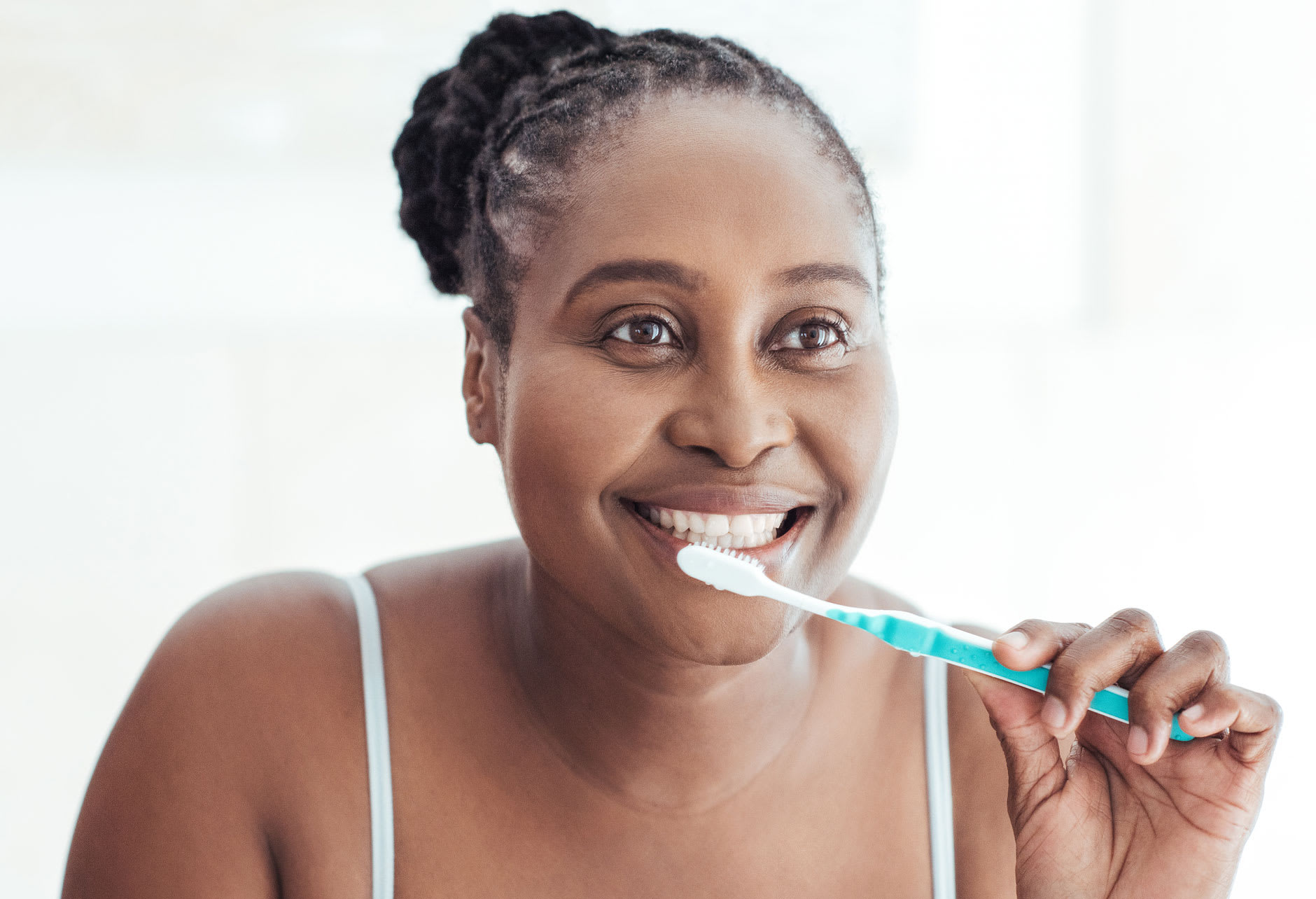 A woman in her 30s is smiling as she holds a toothbrush pretending to brush her teeth, thanks to Fixodent she knows how to remove tartar from dentures and that she needs to remove her dentures first.