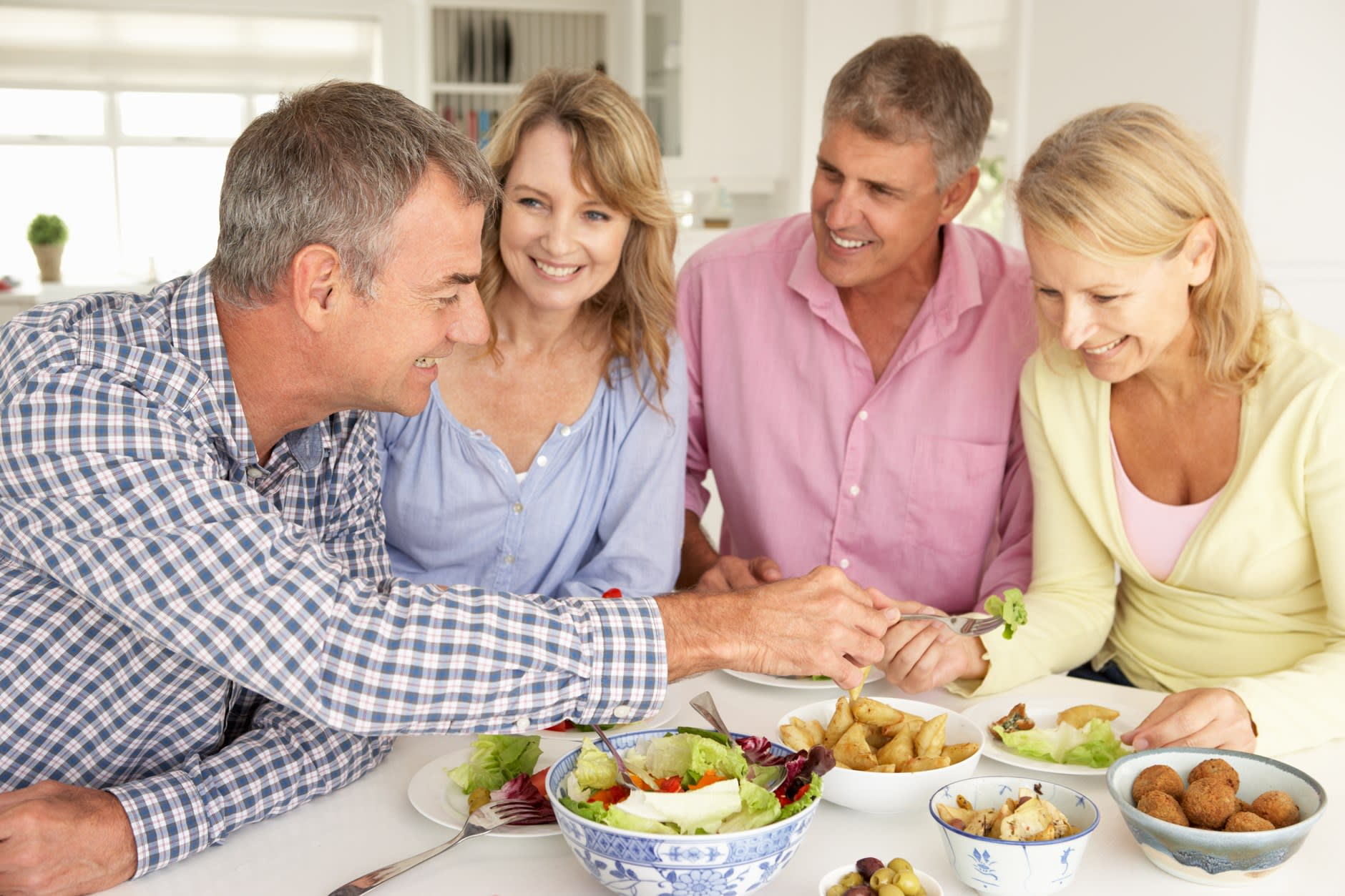A group of friends in their 50s gather about a kitchen table laid out with snacks, one asks what foods he can eat as a new denture wearer.
