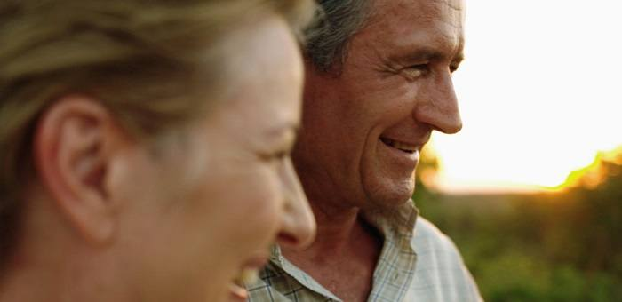 A couple in their 50s laugh outdoors, the man looks relaxed because he has solved the 5 common denture problems with Fixodent.