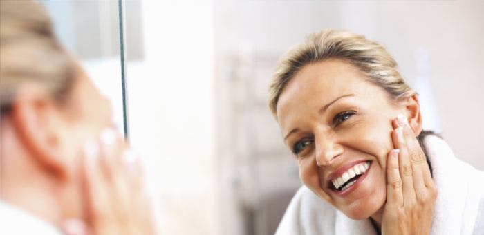 A woman in her 40s is looking into the mirror and smiles with confidence, even though she is wearing dentures, she knows Fixodent will keep them in place and she can still be beautiful.