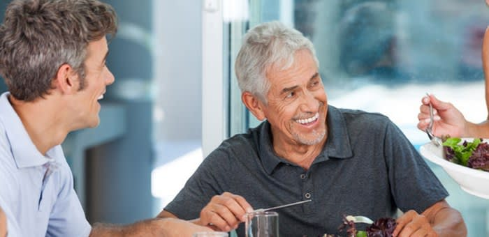 A man in his 50s is at a restaurant and is smiling with friends, as he knows that Fixodent will keep his dentures securely in place, as he creates a new norm with dentures.