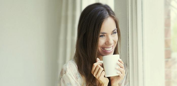 A woman in her 30s is smiling with a mug of coffee as she knows with Fixodent she can still enjoy a natural looking smile with dentures.