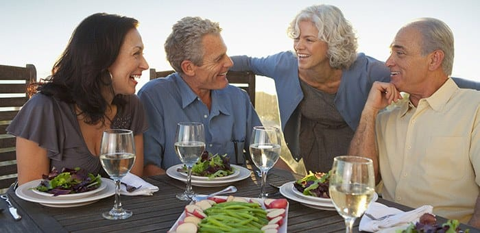 Friends are dining besides the beach and talking. One of them is wearing dentures.  One of the benefits of wearing a denture adhesive cream like Fixodent is being able to enjoy life without worrying about dentures.