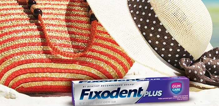 A close up of a striped beach bag, a hat, and a pack of Fixodent denture adhesive. Learn how to use Fixodent denture adhesive to live a full life with dentures.