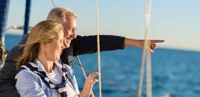 A couple in their 50s are on a yacht, with the man pointing out to sea, he looks on with confidence as he knows that Fixodent will keep his dentures in place and he can shift the focus.