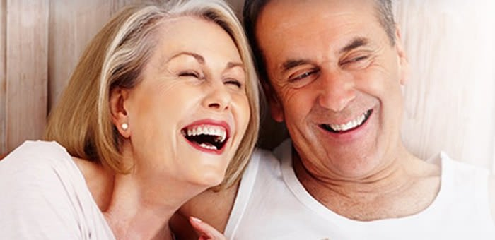 A couple in their 50s are smiling as they know they can rely on Fixodent to help them adjust to life with new dentures.