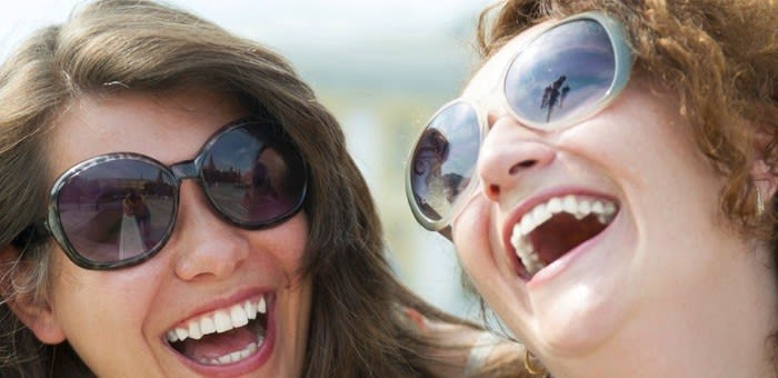 Close up of two women wearing sunglasses and laughing. One of them is wearing dentures, but thanks to Fixodent she can speak with confidence.