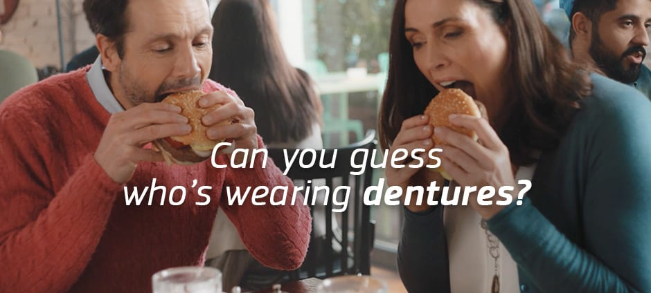 A couple in their 40s are eating a burger. Can you guess who's wearing dentures? With Fixodent, you can't tell.