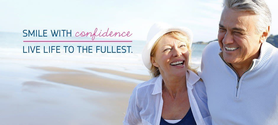 "A couple in their 50s are smiling on the beach with the text ""Smile with confidence and live life to the fullest"" with Fixodent."