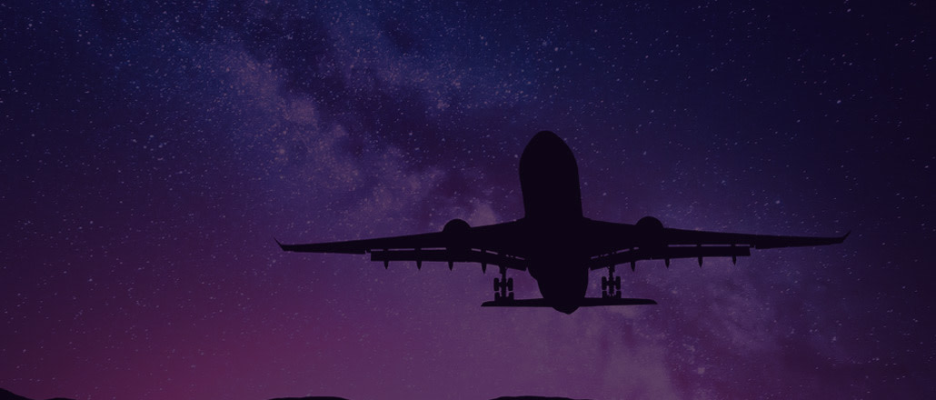 Silhouette of airplane flying at night
