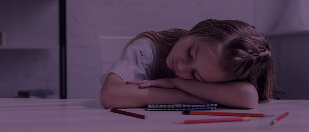 """Kid resting her head on a table with colored pencils."""