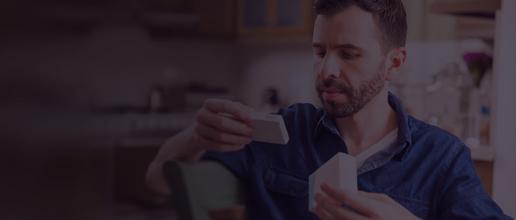 Man looking down and reading prescription label