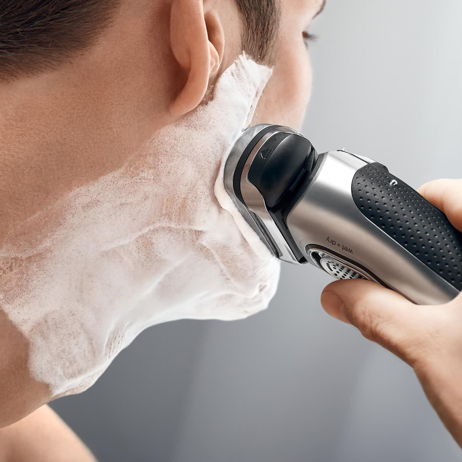 Braun Series 9 silver electric shaver in use