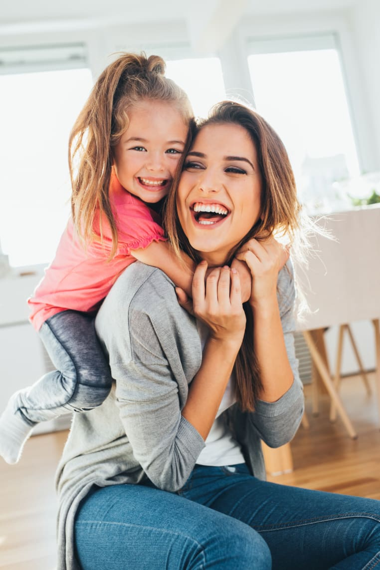 A laughing woman with her smiling daughter