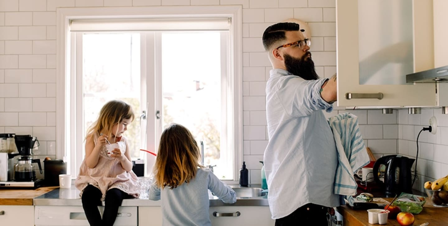 man and kids doing dishes in white kitchen