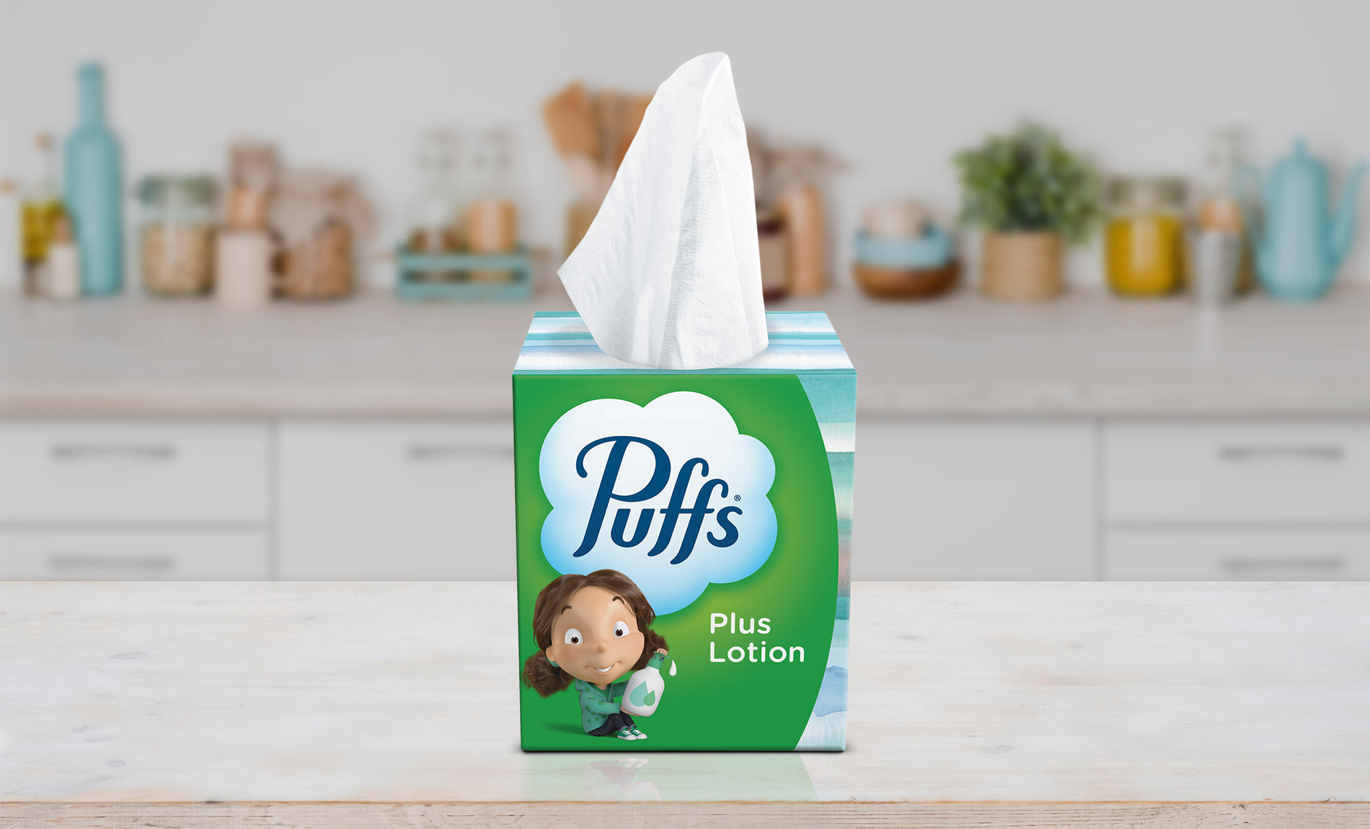 Girl sitting at the table with Puffs Plus Lotion