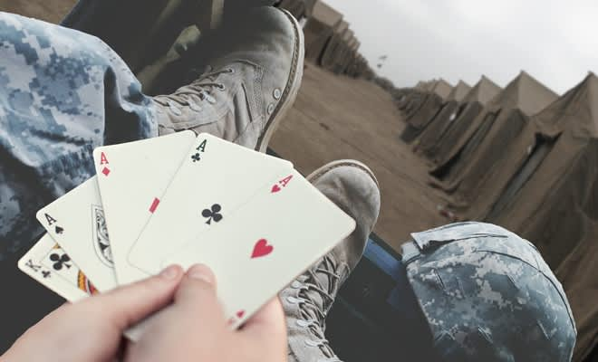 Holding playing cards with a 4 of a kind of aces