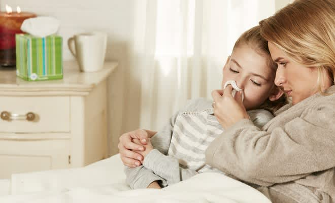 Mother helping her daughter blow her sore nose with Puffs Ultra Soft