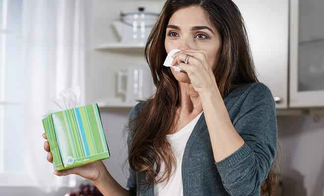 Woman wipes her runny nose with puffs plus lotion