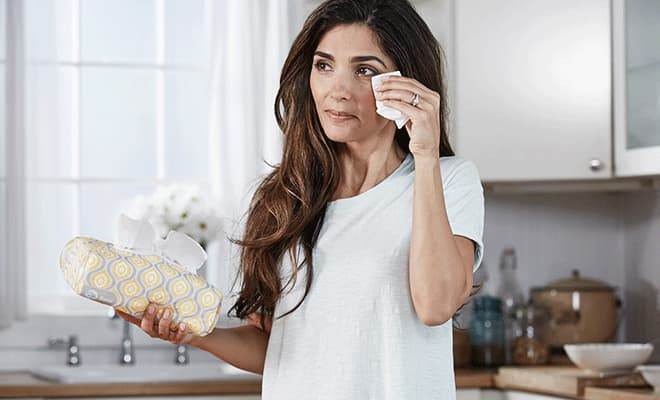 Woman wiping away tears in the kitchen with Puffs soft pack tissue