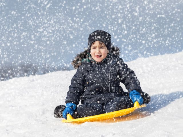 Kind rodelt durch den fallenden Schnee