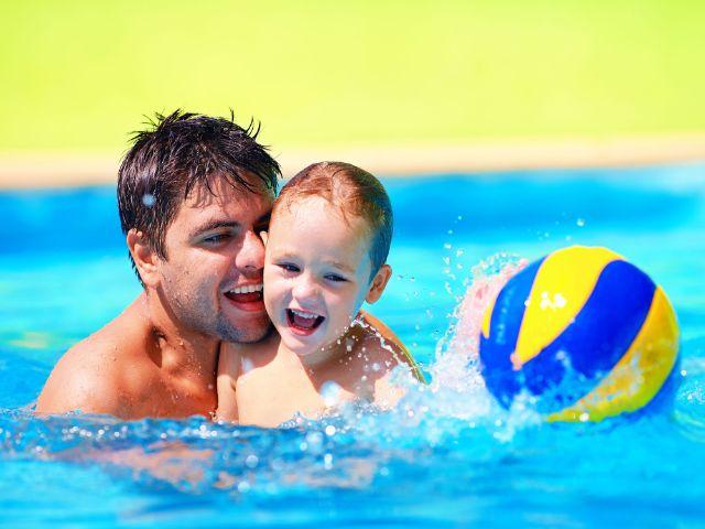 Vater und Kind spielen mit Wasserball
