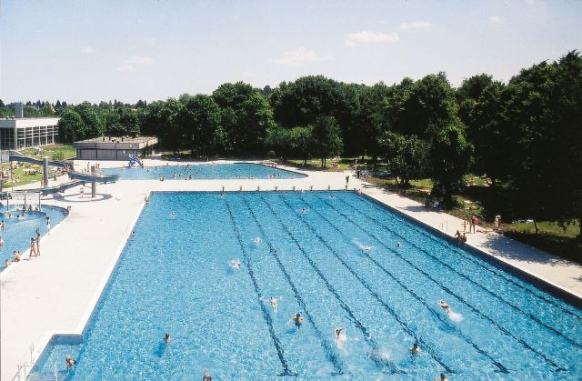 The spacious pools of the Michaeli-Freibad surrounded by large trees.