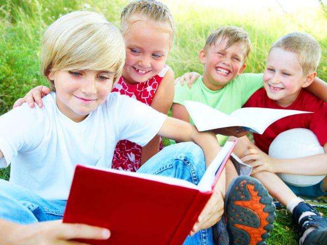 Kinder mit Buch im Gras