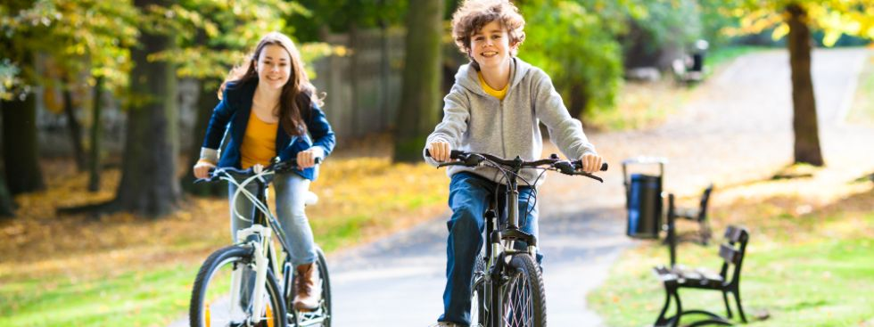 Zwei Kinder fahren mit dem Fahhrad durch einen herbstlichen Park.